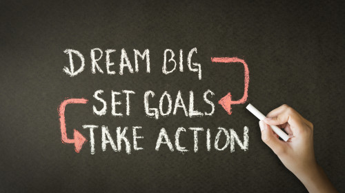 A person drawing and pointing at a Dream Big Set Goals Take Action chalk illustration
